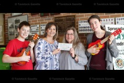 Sprucedale Music Teacher Tarra Green (centre left) accepts a cheque from Your Neighbourhood Credit Union Assistant Branch Manager Mary Pines for the purchase of ukeleles for the Grade 7/8 class. At left is Calob Heinbuch, Grade 8, and at right, Lana Johnston, Grade 7.